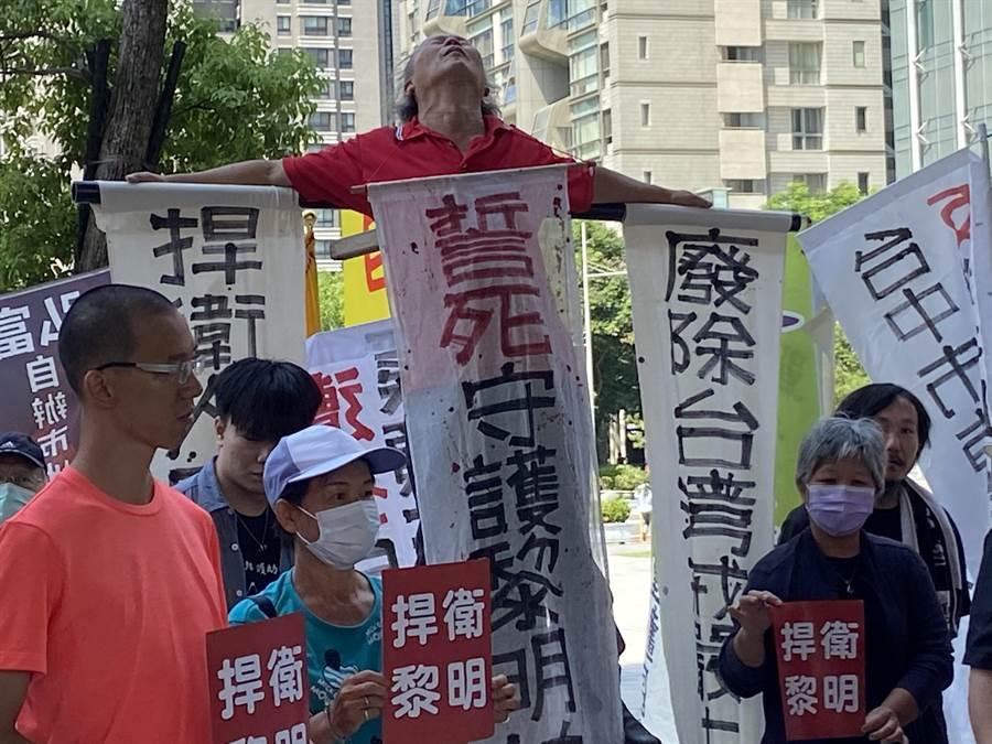黎明幼兒園長林金連13日到市府廣場綁在木字架上抗議。(盧金足攝)