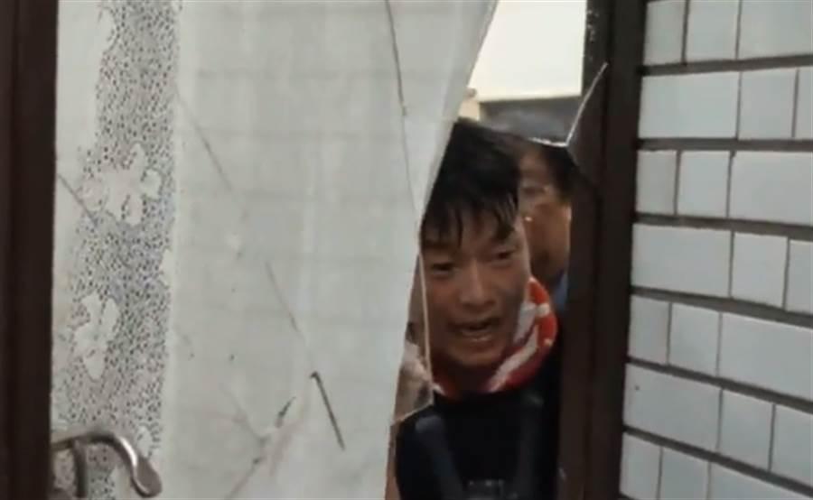 陳柏惟從被敲破的門往外查看。(圖/摘自洪孟楷臉書直播畫面)