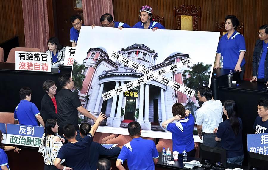 立法院14日臨時會進行監察院長被提名人陳菊資格審查,台灣民眾黨立委將貼有封條的監察院大型海報拿進議場。(姚志平攝)
