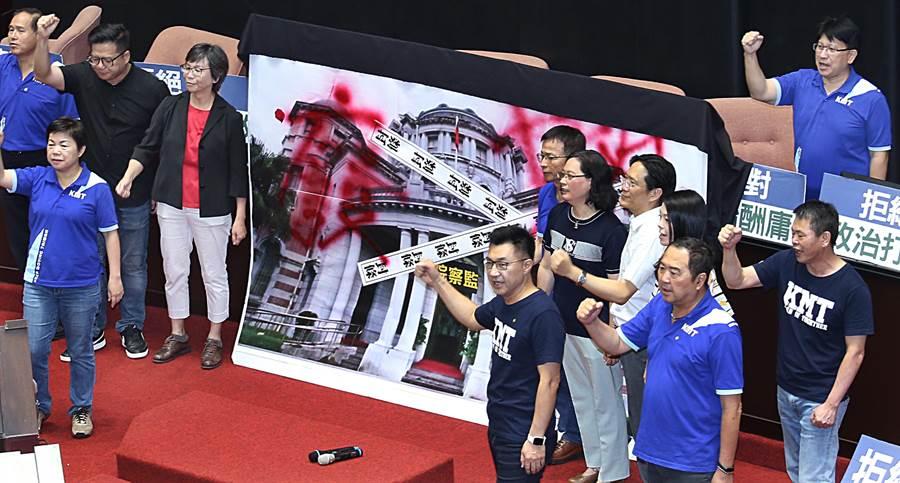 台灣民眾黨立委將貼有封條的監察院大型海報拿進議場並噴上「廢」、「撤」,隨後與國民黨立委一同喊「在野合作,退回陳菊」(姚志平攝)