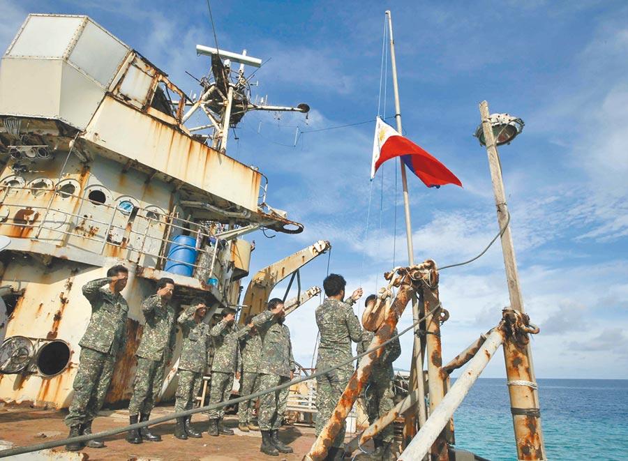 陸菲南海爭端再起!菲律賓外長12日表示,希望北京遵守4年前的國際法庭仲裁。圖為菲律賓軍人在仁愛礁遭菲軍刻意擱淺的艦艇上舉行升旗儀式。(美聯社)
