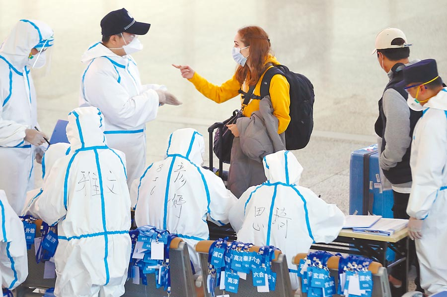 3月16日,身著防護服的工作人員在江蘇祿口國際機場對入境旅客開展新冠肺炎疫情防控工作。(中新社)
