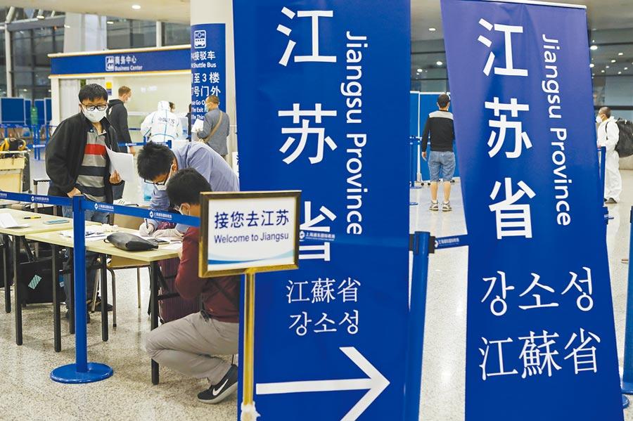 江蘇對台商返蘇的隔離政策採專案處理,圖為3月27日晚,在浦東機場入境轉往江蘇省的人員在進行信息登記。(中新社)