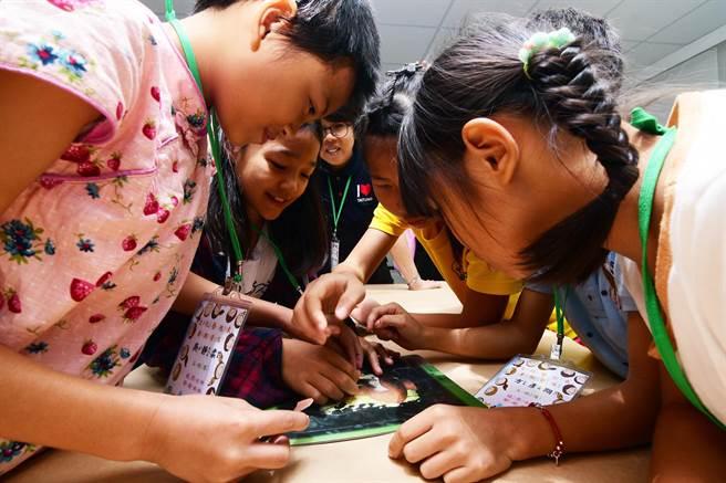 參加史前館暑期營隊的小朋友,用拼圖方式修復陶器,興味盎然。(莊哲權攝)