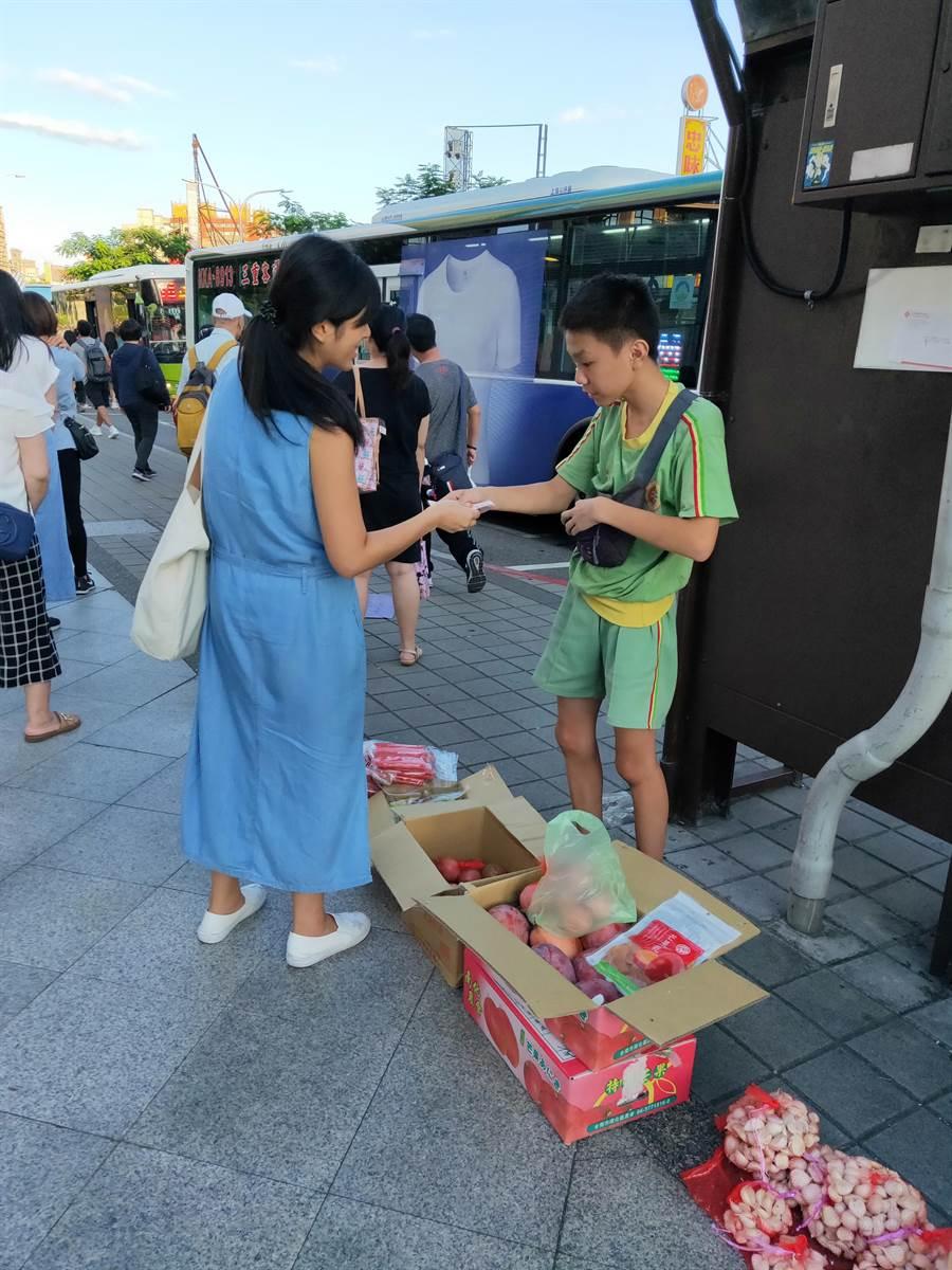 蘆洲半盲國中生街頭幫幾乎全盲的媽媽賣水果。(新北市教育局提供/戴上容新北傳真)