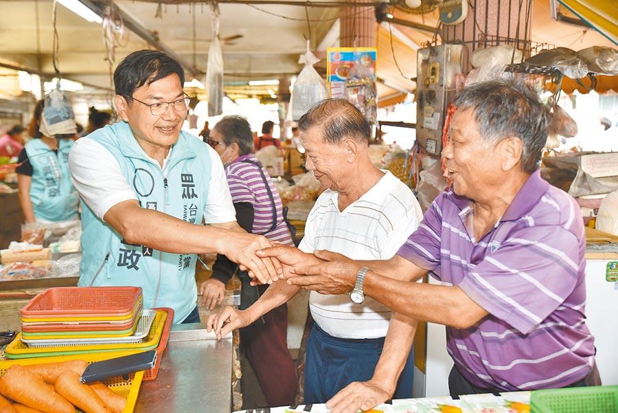 民眾黨高雄市長補選參選人吳益政14日到路竹區一甲大仁路菜市場掃街拜票。(林瑞益攝)