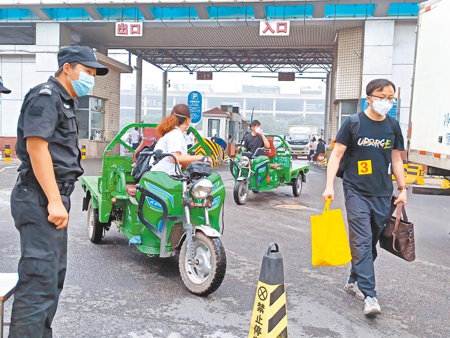 7月12日,北京新發地市場集中隔離的商戶,完成隔離後,回到市場拿取自己的物品。圖為商戶離開新發地市場。(中新社資料照片)