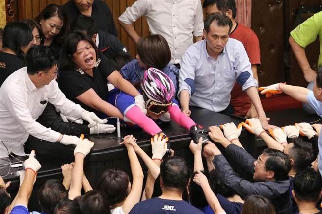 國民黨立委占領議場,民進黨立委16日傍晚進場排除,藍綠雙方爆發衝突,藍委陳玉珍(中戴帽者)堅持到最後一刻,才被綠委拉走。(黃世麒攝)