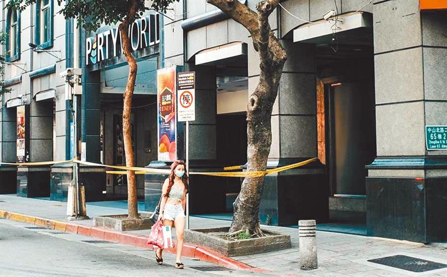 錢櫃大火造成6死慘劇,一位少女從圍著封鎖線的事故現場前經過。(郭吉銓攝)