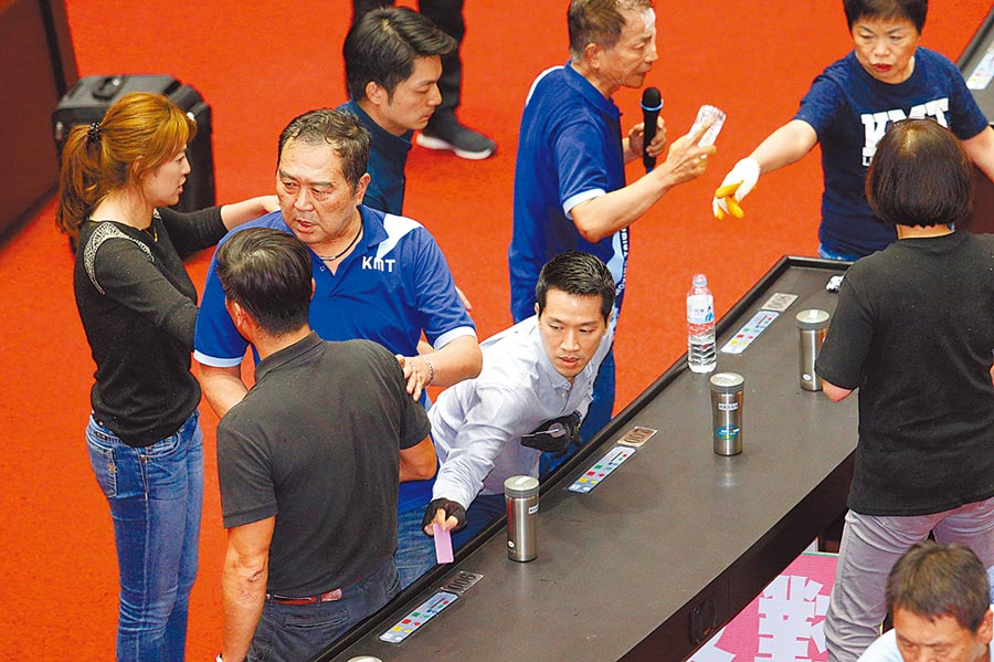民進黨立委何志偉(下)拿著投票卡幫同黨立委投票,引發國民黨立委不滿,直呼綠營作弊。(黃世麒攝)