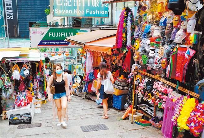 新冠肺炎病毒變種後,傳播率恐提高3成。圖為7月11日,戴口罩的市民經過中環石板街。(中新社)