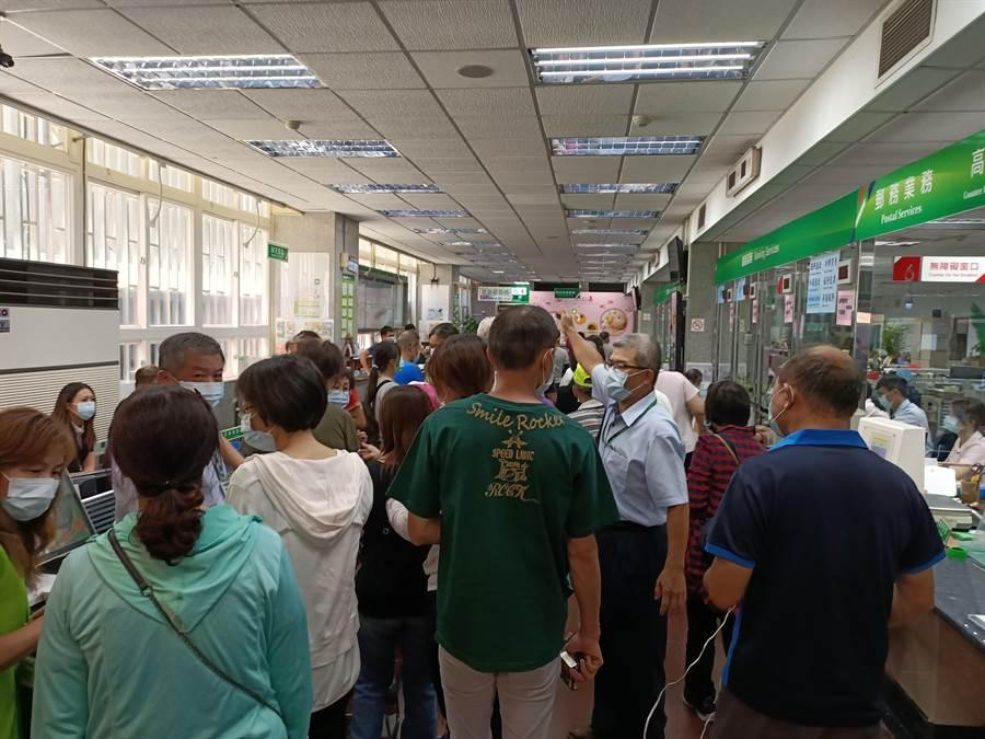 18日上午9點宜蘭郵局一開門,在外等候已久的民眾立即湧入,依號碼牌順序領購三倍券。(胡健森攝)