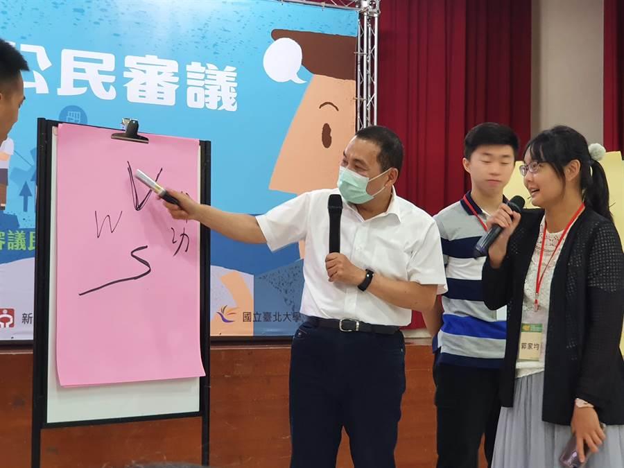 新北市勞工局18日舉辦第1場青年就業公民審議區域會議,市長侯友宜(左一)與青年一起挑戰「畫圖接龍」。(葉書宏攝)