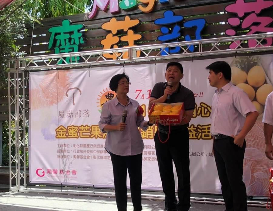 彰化縣長王惠美(左)上台幫忙推廣促銷,為頂級金蜜芒果禮盒拍賣,第一盒就賣出8000元,由彰化縣旅遊產業協會總幹事黃伯裕(右)標得。(主辦單位提供/謝瓊雲彰化傳真)