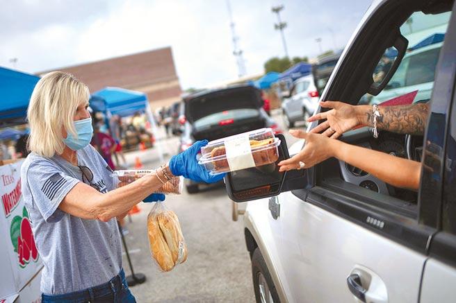 美國德州聖安東尼奧市食物銀行一名志工(左)17日在街頭分發食物給受新冠疫情影響而沒飯吃的民眾。世界衛生組織表示,受疫情影響,今年全球可能有1.32億人遭遇饑餓。(路透)