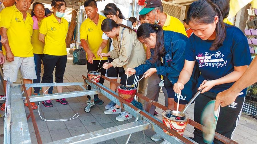 民眾到旗山區糖廠社區體驗煮膨糖。(高雄市農業局提供/林瑞益高雄傳真)