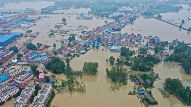 安徽省六安市固鎮鎮因暴雨導致堤壩崩潰,大水淹入4萬多人的鎮上,目前仍有萬餘人被洪水圍困。(圖/新華社)