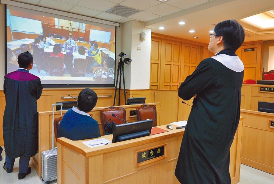 檢辯雙方及被告在中間討論時間,專注看著投影螢幕上審判長與國民法官討論案情。(陳俊雄攝)