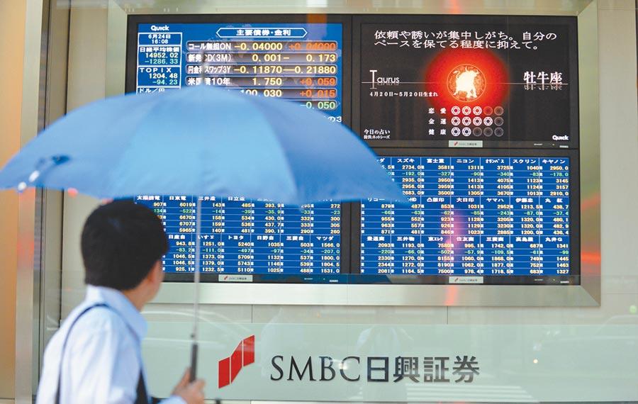 日本東京,一名行人從股指電子顯示屏幕前走過。(新華社資料照片)