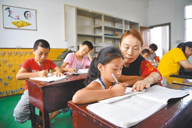 7月17日,因洪水被集中安置的安徽小學生在教師志願者輔導下完成暑假作業。(新華社)