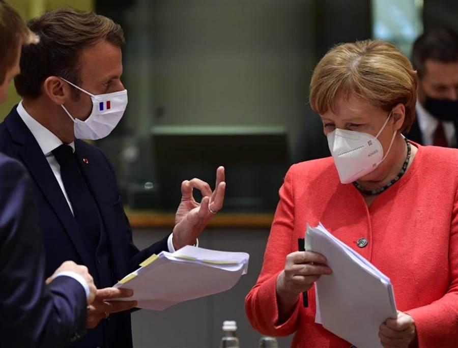 法國總統馬克宏(左)和德國總理梅克爾(右)20日在比利時布魯塞爾的歐盟峰會圓桌會議中,檢視相關文件。(美聯社)