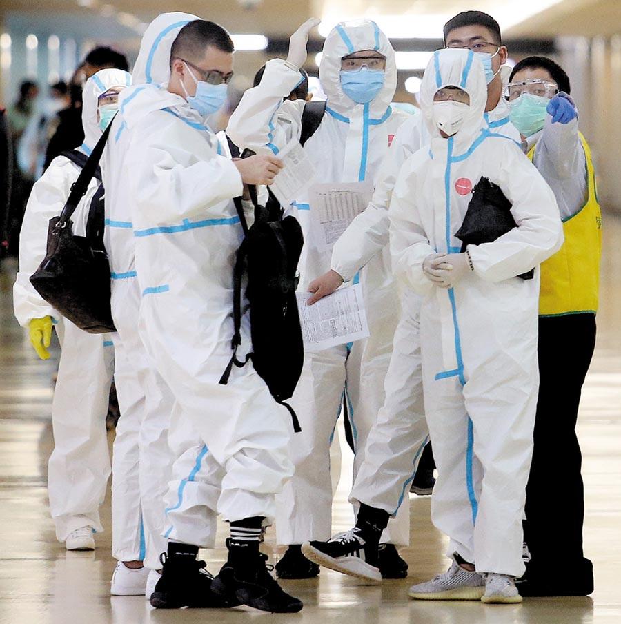 《彭博社》昨天評比世界75個經濟體的防疫表現,台灣成績位居冠軍。圖為一群身穿防護衣的旅客,正準備通關入境。(本報資料照片)