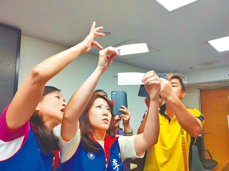 國民黨台南市議員李中岑(中)、王家貞(左)辨識振興三倍券梅花浮水印位置。(洪榮志攝)