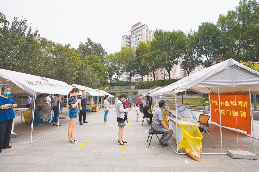 6月24日,醫務人員在北京市西城區手帕口南街核酸檢測集中採樣點進行核酸檢測採樣。(新華社)