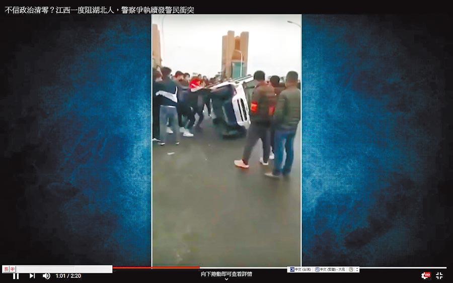 大陸城際管制標準不一,圖為3月27日江西警察在湖北各地陸續解封後拒絕湖北人入境引發衝突;湖北省的警車也被江西警察推翻。(YouTube截圖)