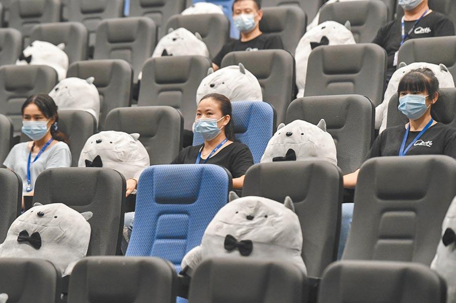 長沙一影城,員工用玩偶擺放在座位之間設置觀影人間隔。(中新社資料照片)