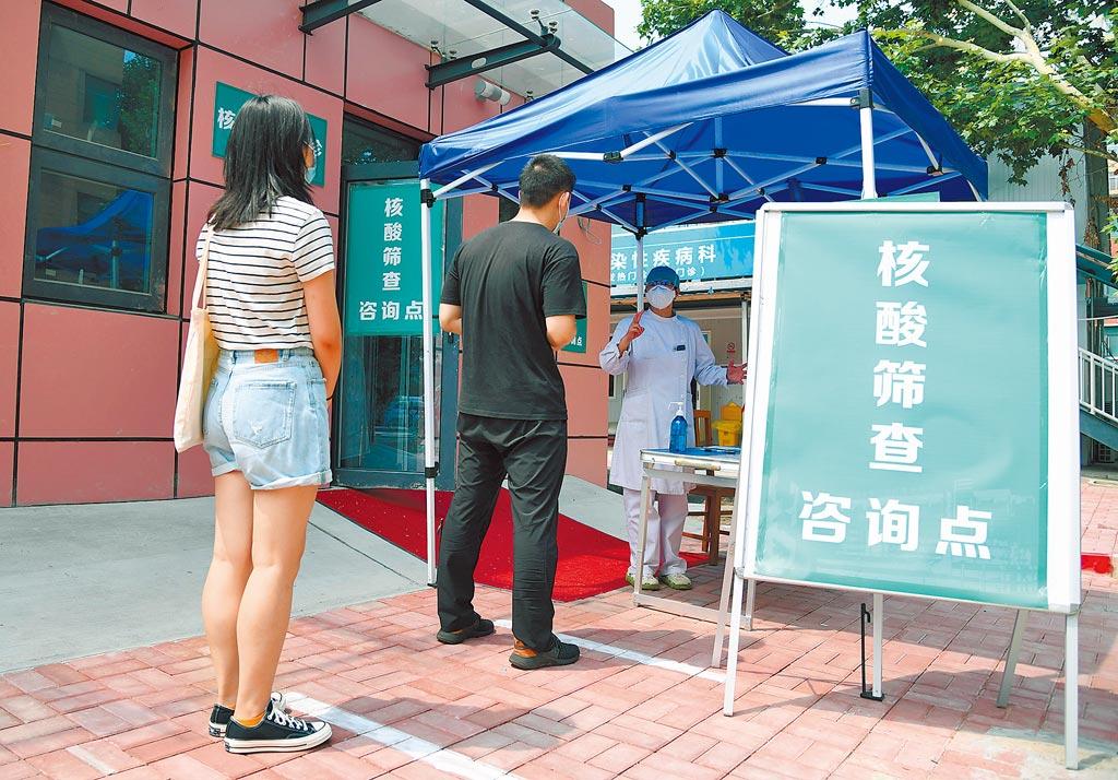 6月20日,北京開展大規模核酸檢測 ,醫護人員在為市民介紹核酸檢測採樣流程。(新華社)