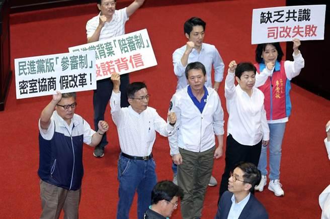 國民黨立委高舉標語並大喊「民進黨反對陪審,全民唾棄」。(姚志平攝)