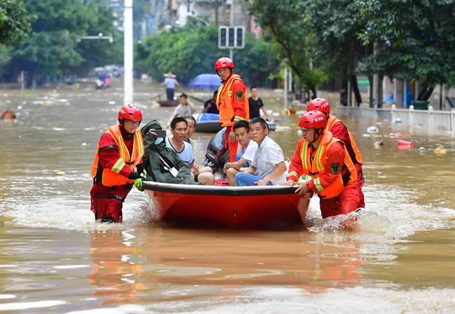 7月11日,廣西融水消防救援大隊的救援人員在轉移被困群眾。(新華社)