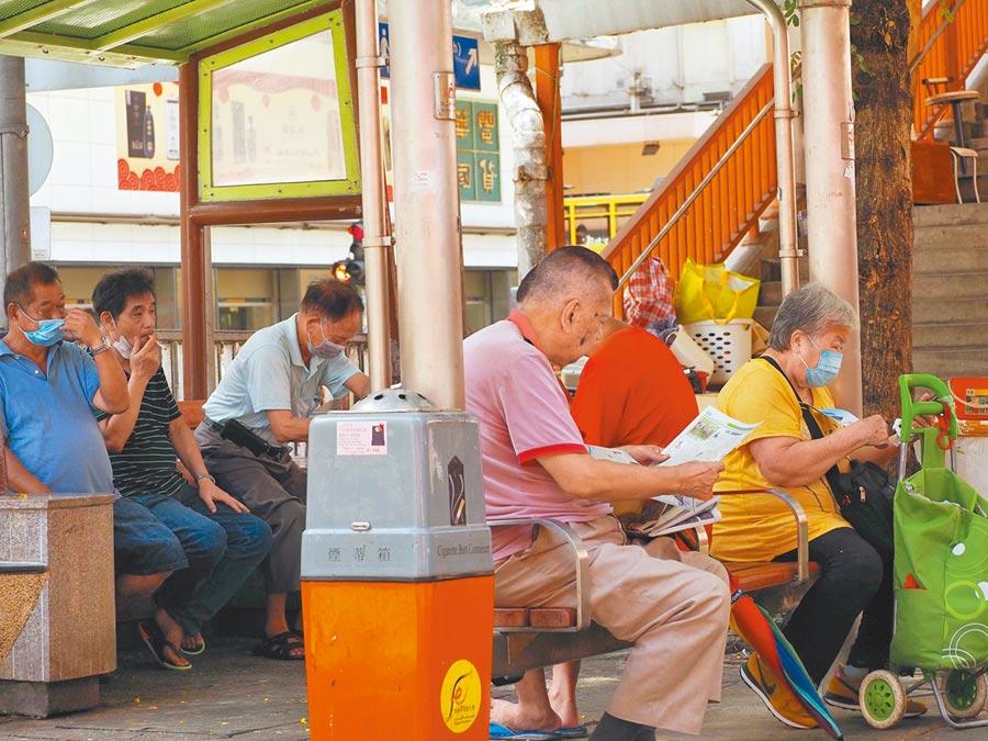 7月21日,雖然香港疫情嚴峻,仍有不戴口罩的市民在讀報或抽菸。(中新社資料照片)