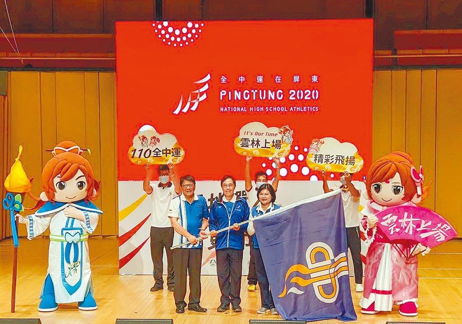 2020全中運23日結束,在屏東演藝廳舉行閉幕典禮,縣長潘孟安(前左)將會旗交棒給明年辦理的雲林縣長張麗善(前右)。(潘建志攝)
