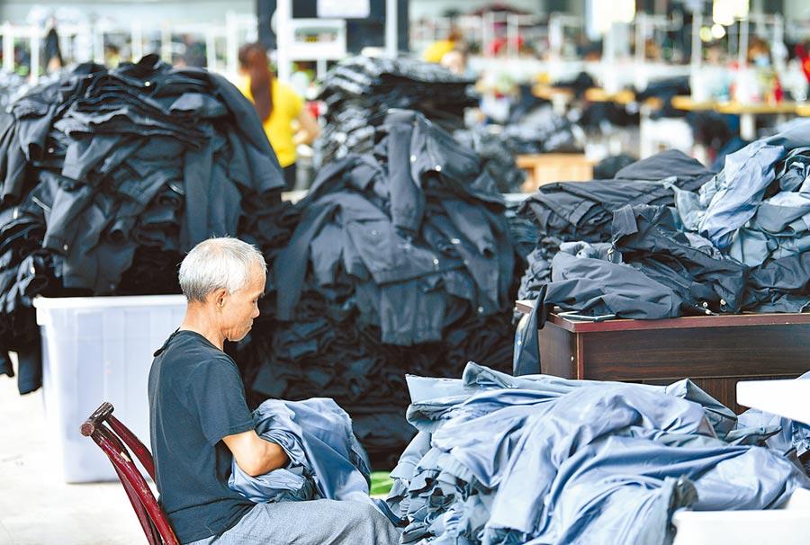 大陸年底要達成全面脫貧目標,貨幣不致很緊縮。圖為湖北扶貧工廠,農民在製衣生產線上工作。(新華社)