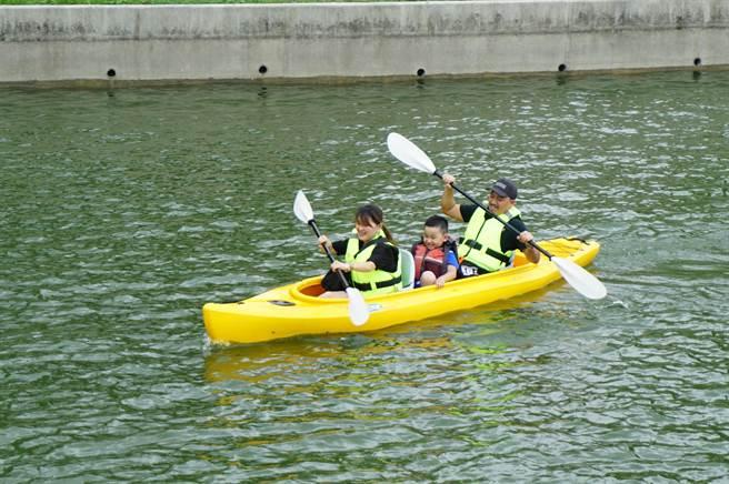 親子檔3人乘坐獨木舟體驗,划槳手忙腳亂。(王文吉攝)