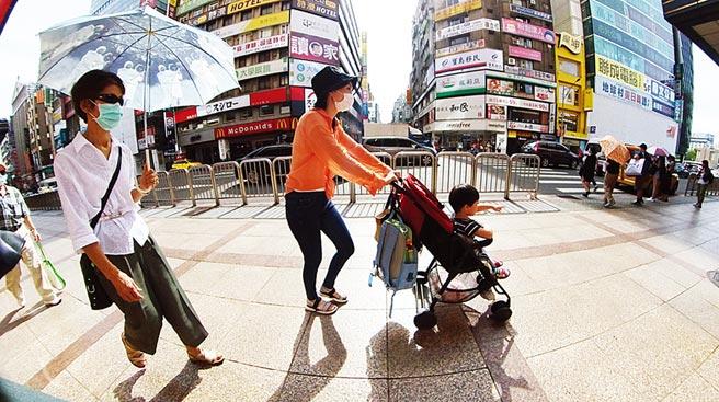 根據中央氣象局資料,台北觀測站24日午後氣溫測得攝氏39.7度,創下台北站創站以來的最高氣溫紀錄,民眾撐著傘在烈日下移動。(姚志平攝)