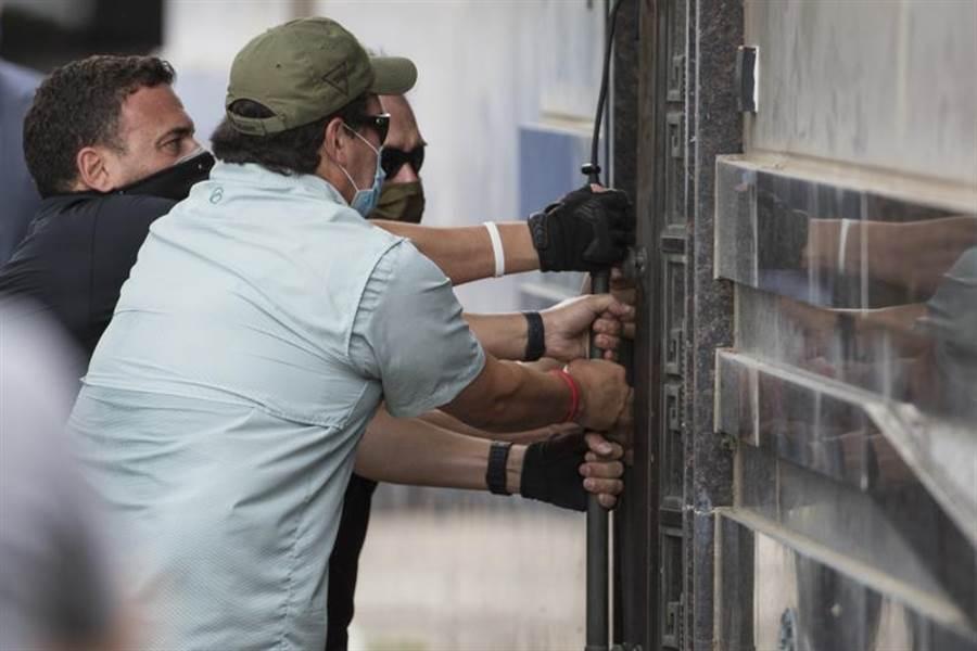 據路透社報導,隨著美方要求陸駐休士頓領事館於24日閉門期限已到,一群美國官員正在強開大門。(美聯社)