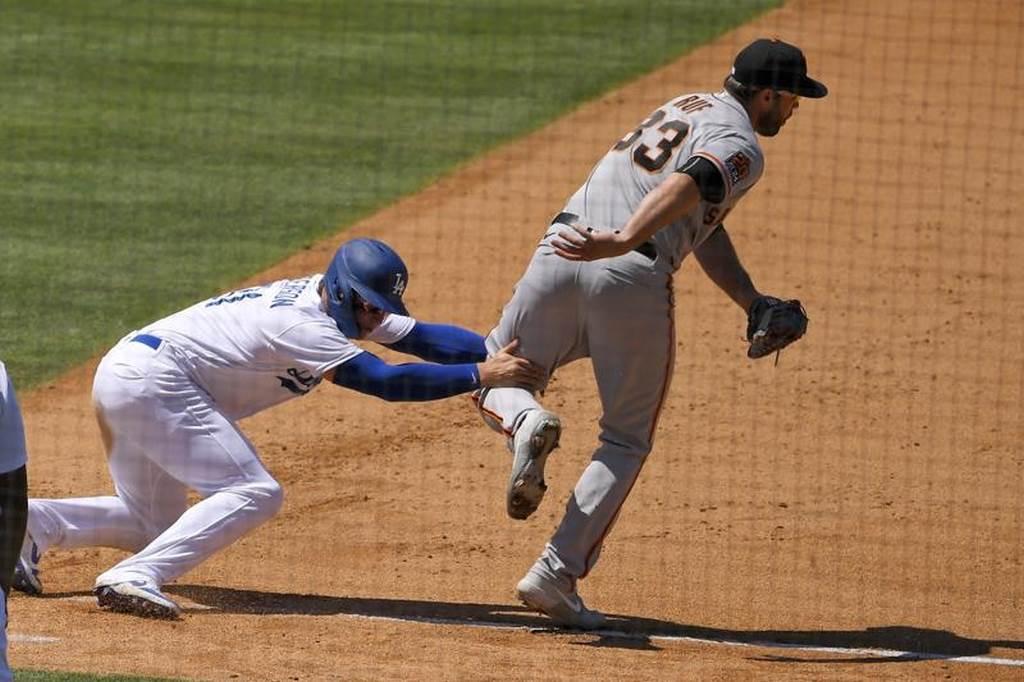 道奇彼德生回一壘失敗遭封殺,伸手抓住巨人一壘手拉夫的腿。(美聯社)