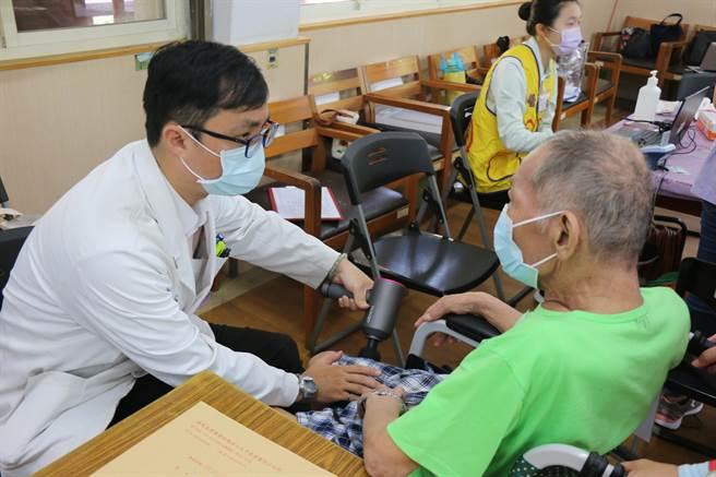 台中慈濟醫院中醫師陳智聖 (左) 使用筋膜槍為為市立仁愛之家住民按摩。(台中慈濟醫院提供/王文吉台中傳真)