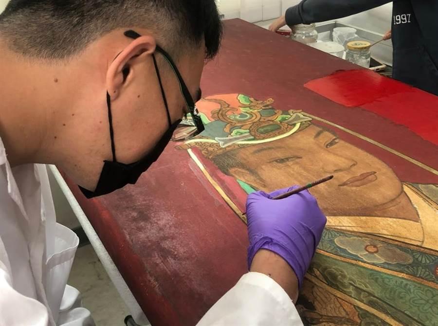 台南藝術大學修復團隊為台南白河永安宮門神加固皺縮彩繪層。(台南市文資處提供/劉秀芬台南傳真)