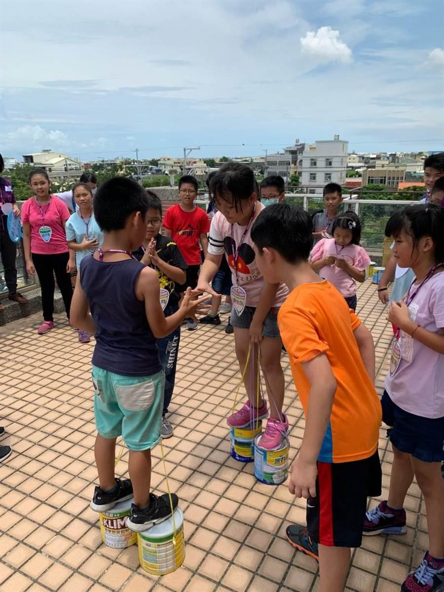 童玩市集闖關遊戲「踩高蹺」,讓參與學童玩的不亦樂乎。(北台中家扶中心提供/王文吉台中傳真)