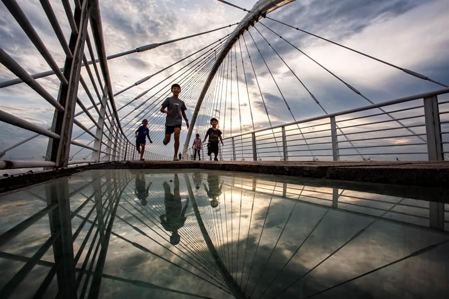 不少攝影師利用橋上兩旁的透明玻璃反射取景。(新竹市政府提供/陳育賢新竹傳真)
