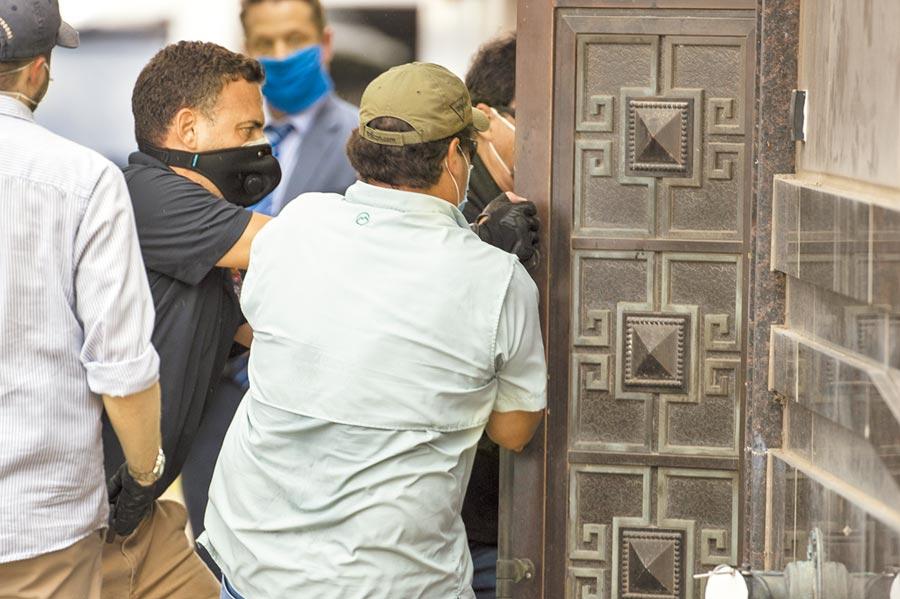 一群人正用力拉開門,以便進入已人去樓空的總領事館。(美聯社)
