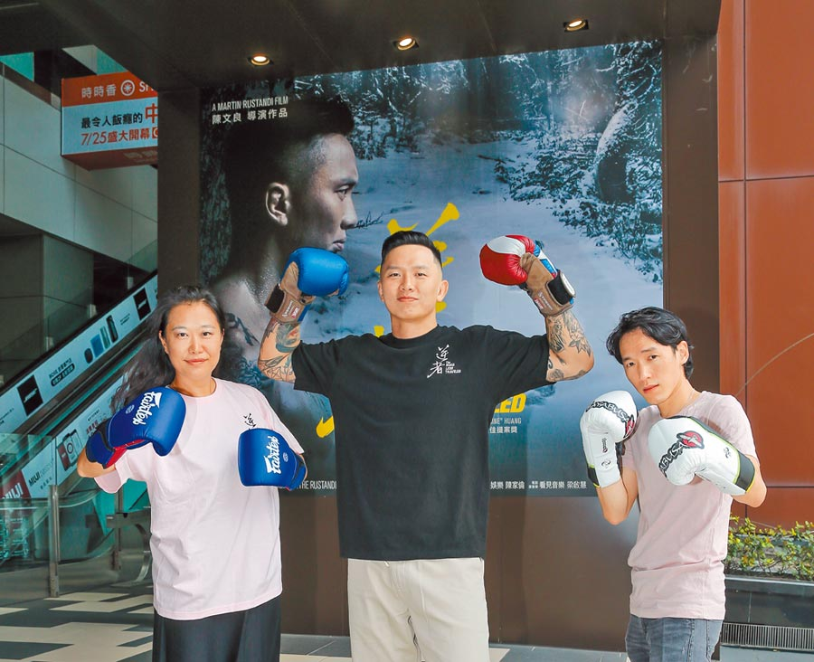 音樂人梁啟慧(左起)、男主角黃育仁、導演陳文良在南港喜樂時代影城外的電影大看板合影。  (盧禕祺攝)