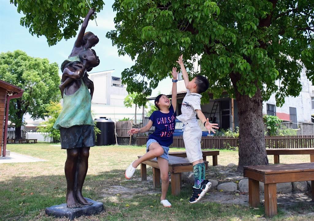 台東市民權里日式建築的茄冬樹下,多了栩栩如生的「捕蟬」銅雕,小朋友也跟著雀躍。(莊哲權攝)
