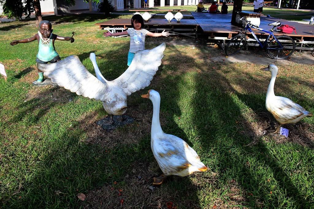 台東美術館水池旁,小孩與大白鵝的決鬥,栩栩如生,真實中的小女孩也來助陣。(莊哲權攝)