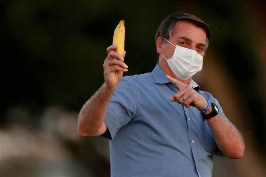 巴西新冠肺炎疫情迅速蔓延,確診人數不斷飆升,連總統波索納洛(Jair Bolsonaro)也染疫,圖為他7月24日在首都巴西利亞的官邸晨曦宮(Alvorada Palace)高舉香蕉的神情。(路透)