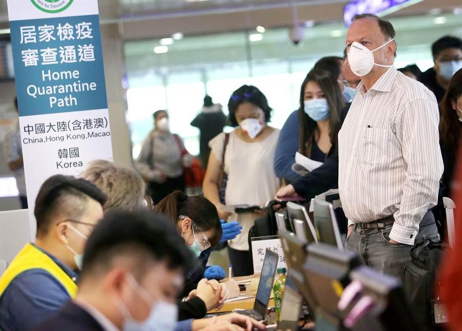 圖為1群外籍旅客正在排隊查驗健康聲明書。(資料照,范揚光攝)
